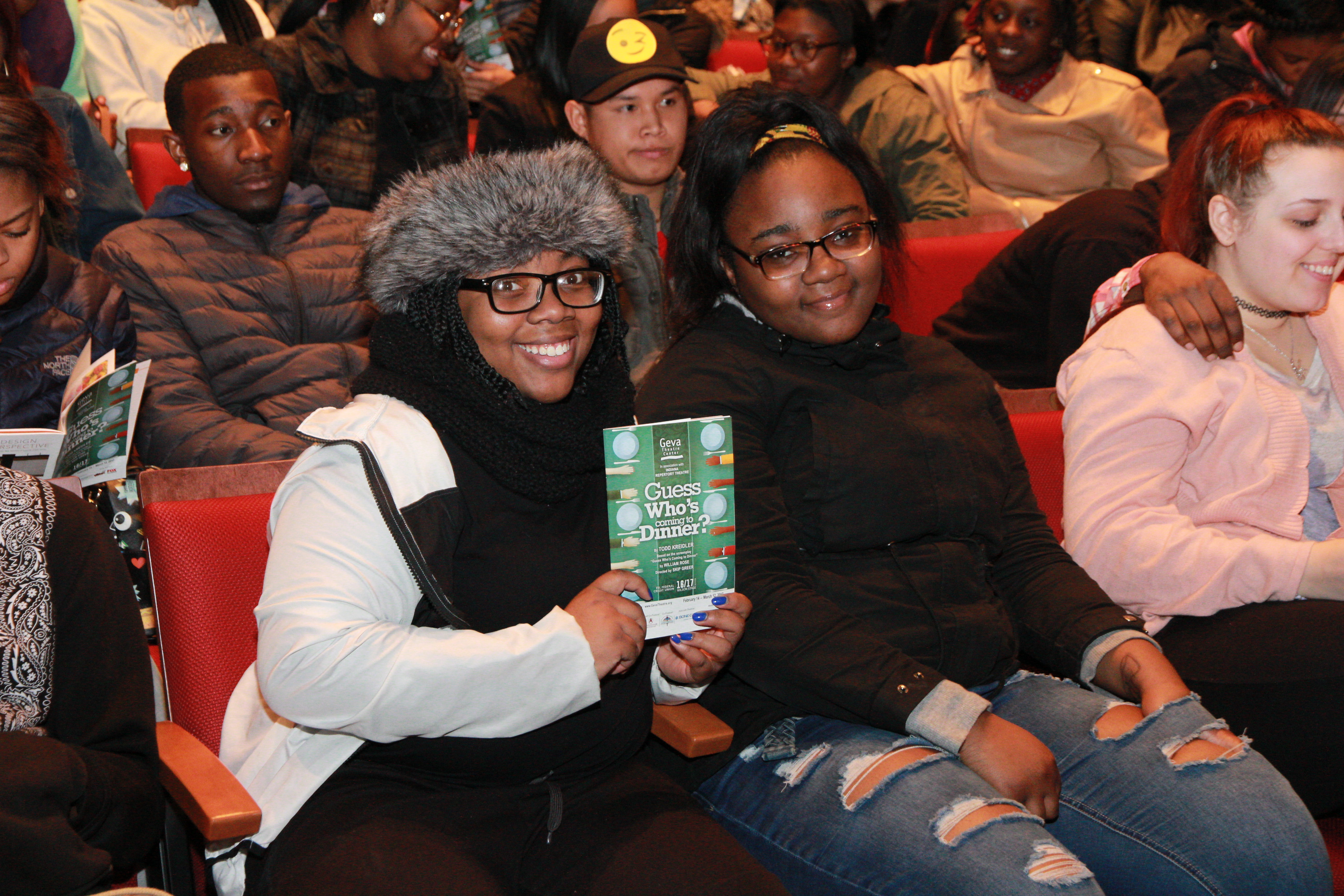 Two young women hold up a playbill in the audience at Geva Theatre Center
